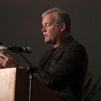 Puhujapöntössä seisova Lee Berger pitelee käsissään Homo nadalin rekonstruoitua kalloa.