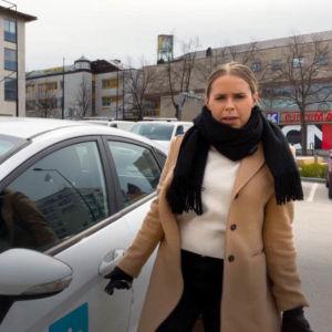 En kvinna vid en parkerad bil.