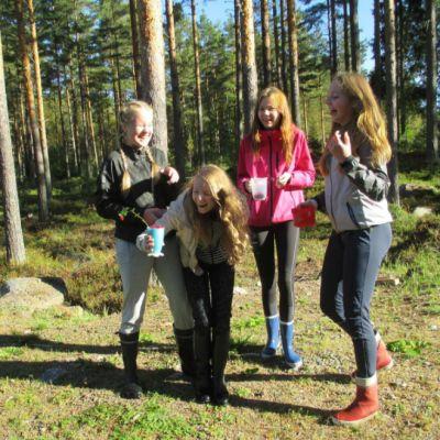 Kuvassa neljän nuorta metsässä.