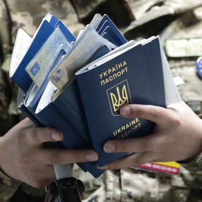 Maastopukuinen henkilö pitelee Ukrainan passeja käsissään.