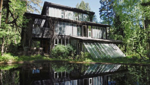 Bruno Erats året runt hus med många fönster speglas i vattnet