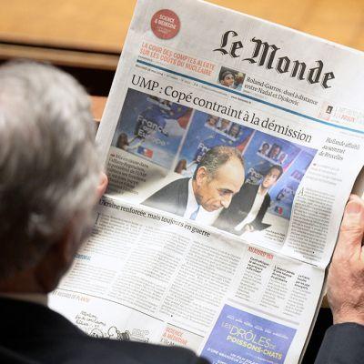 Ranskan parlamentin jäsen lukee Le Monde-lehteä, jonka etusivulla on uutinen UMP:n vaalirahaskandaalista. Kuva on otettu 27. toukokuuta.