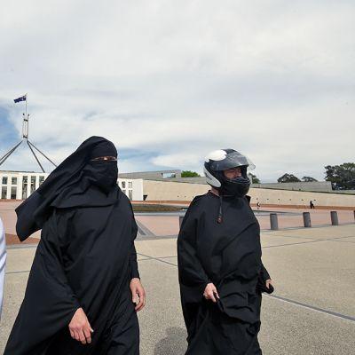 kolme miestä, jotka ovat peittäneet kasvonsa Ku Klux Klanin hupulla, niqab-hupulla ja moottoripyöräkypärällä