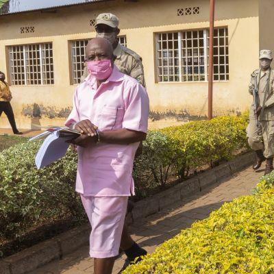 Kuvassa etualalla kävelee Paul Rusesabaguna vaaleanpunaisessa vangin asussa. Hänen takanaan kävelee kolme vartijaa.