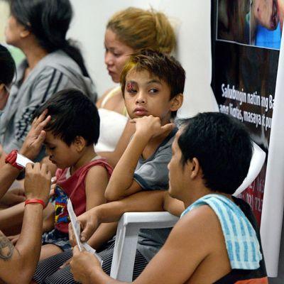 Isä lohdutti ilotulituksessa haavoittunutta poikaansa Jose Reyesin sairaalassa Manilassa aikaisin torstaiaamuna.