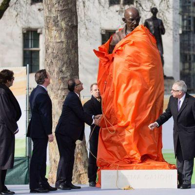 Intialaisnäyttelijä Amitabh Bachchan (vas.), Iso-Britannian pääministeri David Cameron ja Gandhin lapsenlapsi Gopalkrishna Gandhi (oik.) seuraavat kun Intian valtionvarainministeri Shri Arun Jaitley paljastaa Mamathan Gandhin pronssisen patsaan parlamenttiaukiolla Lontoossa 14. maaliskuuta.