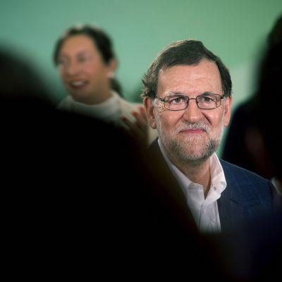 Silmälasipäinen Mariano Rajoyseisoo kahden mustan varjomaisen hahmon keskellä. Taustalla kuvassa näkyy häimeänä hahmona nainen. Taustaväri on vihreä.