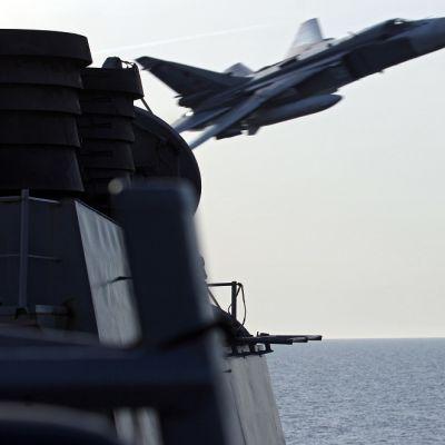 Venäläinen lentokone syöksyy kuvan vasemmassa reunassa olevan aluksen ohi. Kuva on otettu yhdysvaltalaisen sotilasaluksen kannelta.