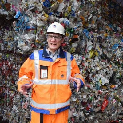 Mies kertoo Ekokemin Muovijalostamosta muovijätepaaleja taustallaan