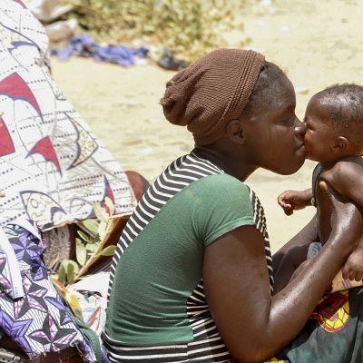 Nuori nainen suutelee pientä lasta, joka istuu hänen sylissään.