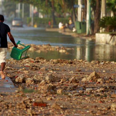 Kuvassa mies kävelee selin kameraan kadulla, jolla on mutaa ja romua.
