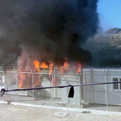 Tulipalo piikkilanka-aidan takana pakolaisleirillä