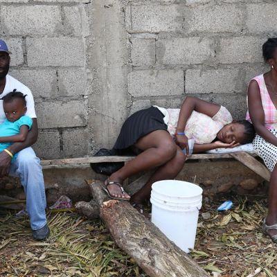 Koleraan sairastuneita ihmisiä istuu puisilla penkeillä ulkona.