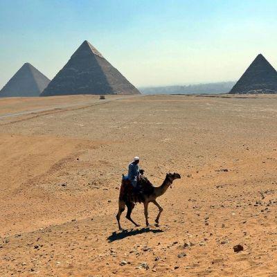 Turistiopas ratsastaa kamelilla Gizan pyramidien edustalla.