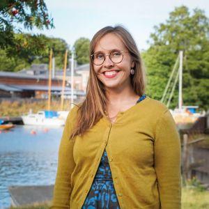 en kvinna i brunt långt hår, glasögon och gul tröja står vid en hamn med båtar i bakgrunden