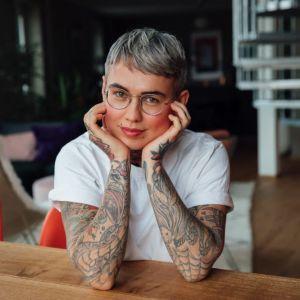 Somevaikuttaja Nata Salmela kotonaan keittiönpöydän ääressä nojaamassa käsiinsä.