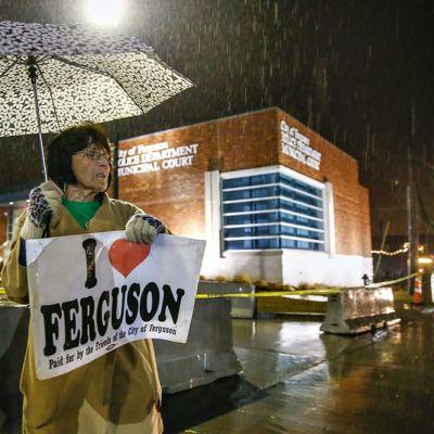 Fergusonin asukas Kathy Magrecki  seisoo sateessa poliisilaitoksen edessä.