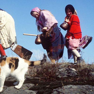 Pääsiäisnoidiksi pukeutuneet lapset leikkivät lentävänsä luudilla.