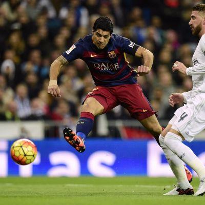 Barcelonan Luis Suarez laukoo Real Madridin Sergio Ramosin edestä.
