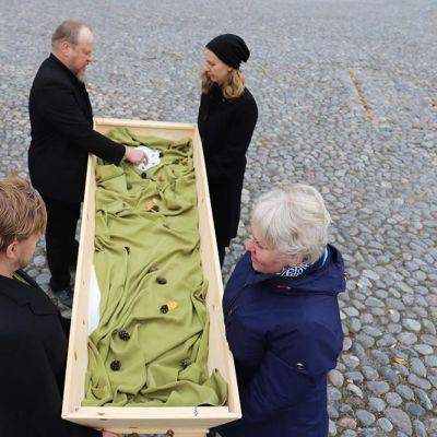 Neljä seurakunnan työntekijää kantaa arkkua Elokapinan kanssa järjestettävässä mielenilmauksessa