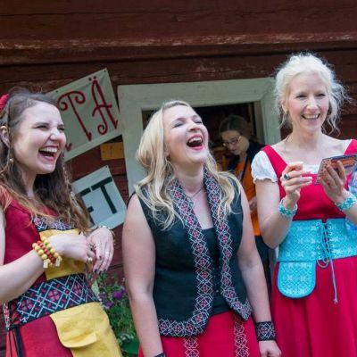Värttinän kolme naislaulajaa nauraa esiintymisasuissaan.