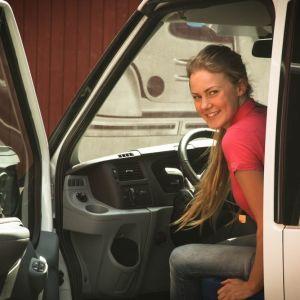 Nainen katsoo pakettiauton avoimesta ovesta