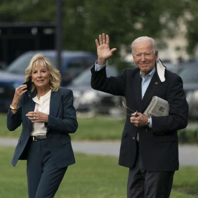 Joe ja Jill Biden ulkona maskit puoliksi kasvoillaan, Joe Biden huiskuttaa kameralle.