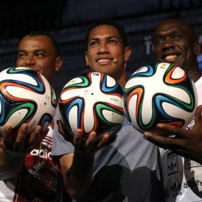 Kolme 2014 MM-kisojen virallista pelipalloa Brazucaa Cafun (vas.), Hernanen (kesk.) ja Clarence Seedorfin (oik.) käsissä.