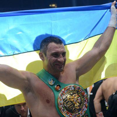 Nyrkkeilijä Vitali Klitschko poseeraa Ukrainan lipun ja mestaruusvyön kanssa.