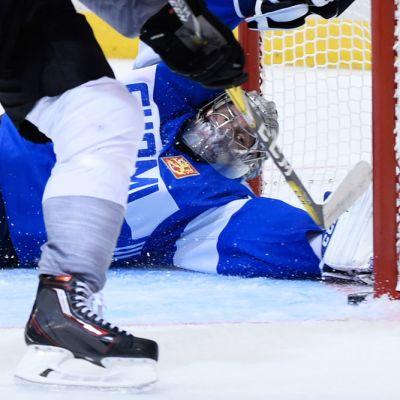 Pekka Rinne kurottaa kiekkoon.