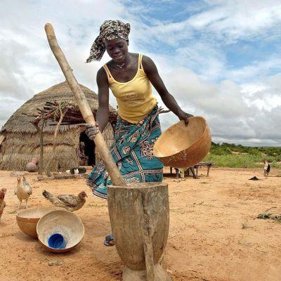 Nainen valmistaa perinneruokaa ulkona pienessä kylässä. Taustalla kanoja ja pieniä asuntoja.