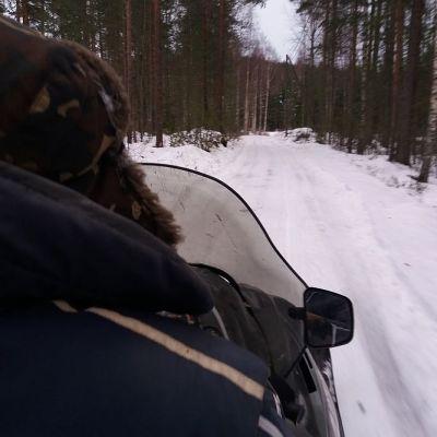 Mies ajaa metsässä moottorikelkalla.