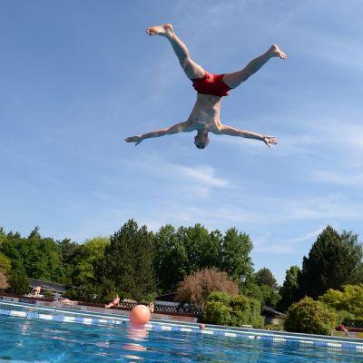 Kuvassa mies hyppää veteen.