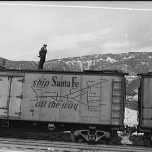 Seisovan tavarajunan katolla poseeraava rautatietyöläinen Kaliforniassa, 1943