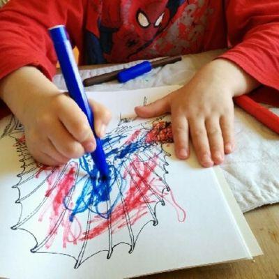 Lapsen kädet näkyy, kun hän värittää värityskirjaa.