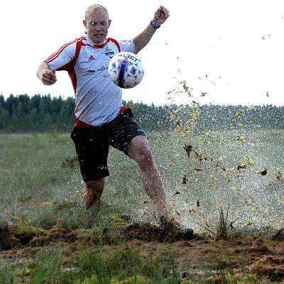 Anssi Kumpula potkaisee, ja Pekka Koskela säntää pallon perään suopotkupalloilun harjoituksissa Seinäjoen Peräseinäjoella.