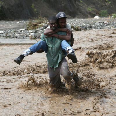 Toista miestä reppuselässä kantava mies kahlaa polviaan myöten mutaisessa vedessä.