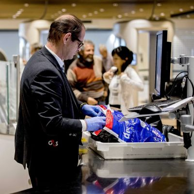 Turvatarkastaja tutkii matkatavaroita laitteella