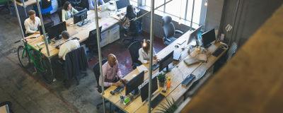 Människor på ett kontor jobbar. Bilden är tagen ovanifrån.