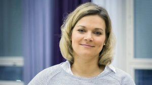 Erika Strandberg i grå tröja lutandes mot ett bord.