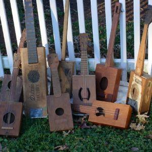 Flera gitarrer, banjon och ukulelen gjorda av cigarrlådor står uppställda mot ett staket utomhus.