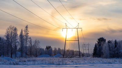 Kraftledning i Limingo och solen skymtar bakom molnen och det finns snö på marken.