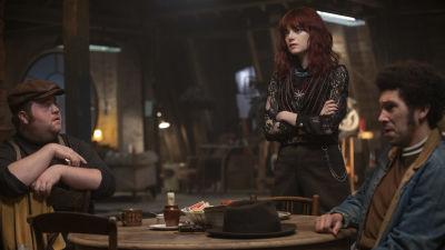 Horace (Paul Walter Hauser), Estella (Emma Stone) och Jasper (Joel Fry) sitter runt ett bord.