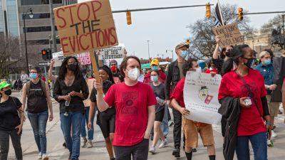 """Demonstranter marscherar på gatan. En bär en skylt där det står """"Stoppa vräkningarna""""."""