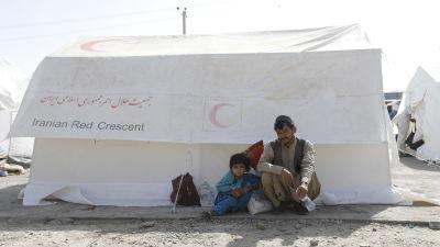 Två personer sitter vid ett tält på gränsen mellan Afghanistan och Iran.