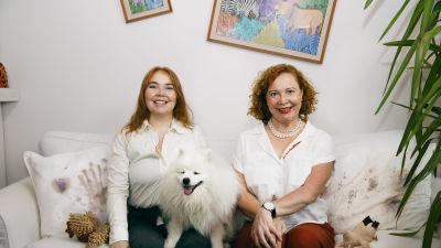 Vivi och Heidi sitter i soffan med hunden mellan sig. I bakgrund syns porträtt på sned och de smår stelt och påklistrat.