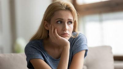 Blond kvinna lutar hakan i handen och ser fundersam ut