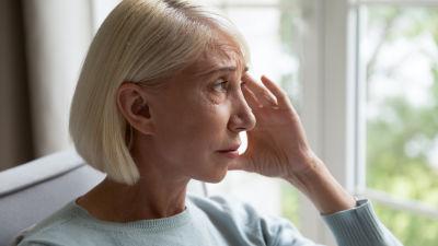 Blond medelålderskvinna i profil vid fönster, ser sorgsen ut