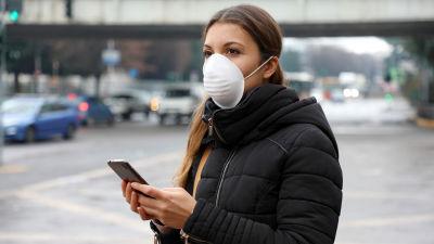 En kvinna använder sin mobiltelefon på stan.