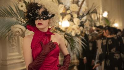 Cruella (Emma Stone) ser förvånad ut i en röd galadress på en maskerad.